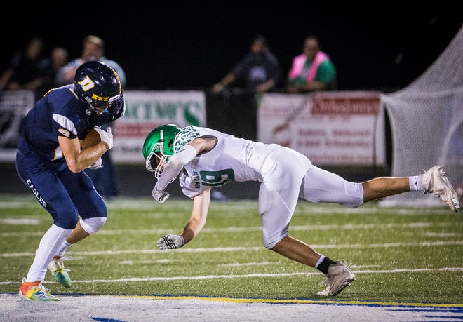 FILE -- New Castle's Layne Nicholson (right) goes in to tackle a Delta ball carrier during their game at Delta High School Friday, Sept. 27, 2019.