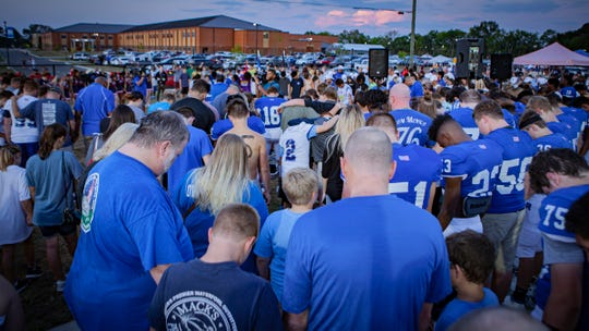 A large group of Rockvale High students and parents led a prayer prior to Friday's game against Oakland.