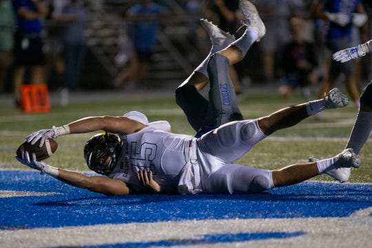Naples High School's Dominic Mammarelli lands on the end zone after catching a 17-yard pass to score a touchdown against Barron Collier High School, Friday, Sept. 27, 2019, at Barron Collier High School.