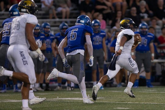 Naples High School's Elan Sommala carries the ball against Barron Collier def, Friday, Sept. 27, 2019, at Barron Collier High School.