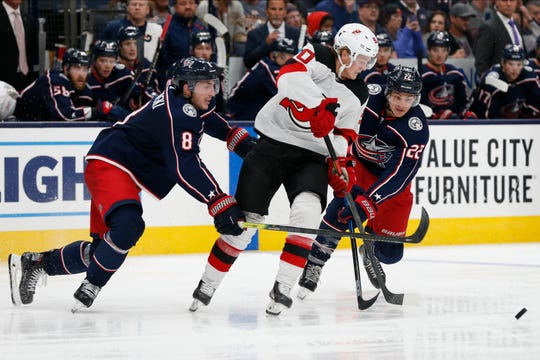 New Jersey Devils' Jesper Boqvist, center, of Sweden, tries to skate between Columbus Blue Jackets' Zach Werenski, left, and Sonny Milano during the third period of an NHL preseason hockey game Friday, Sept. 27, 2019, in Columbus, Ohio.