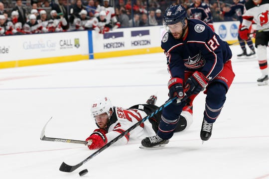 New Jersey Devils' Damon Severson, left, dives to try and knock the puck away from Columbus Blue Jackets' Oliver Bjorkstrand, of Denmark, during the second period of an NHL preseason hockey game Friday, Sept. 27, 2019, in Columbus, Ohio.