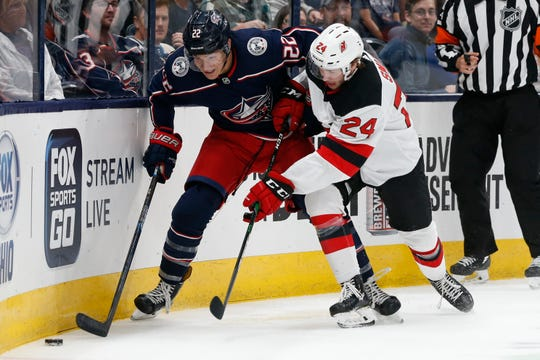Columbus Blue Jackets' Sonny Milano, left, and New Jersey Devils' Ty Smith fight for the puck during the second period of an NHL preseason hockey game Friday, Sept. 27, 2019, in Columbus, Ohio.