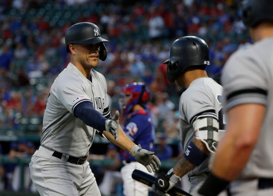 New York Yankees' Giancarlo Stanton, left, and DJ LeMahieu celebrate Stanton's solo home run against the Texas Rangers in the first inning of a baseball game in Arlington, Texas, Friday, Sept. 27, 2019. (AP Photo/Tony Gutierrez)