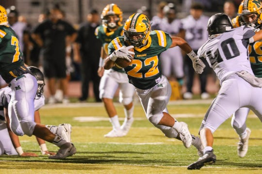 Senior running back Mathew Riley (22) runs the ball as the Mayfield Trojans face off against the Oñate Knights at the Field of Dreams in Las Cruces on Friday, Sept. 27, 2019.