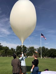 Paulo Oemig, center, New Mexico Space Grant Consortium research scientist, holds a high-altitude balloon during a test on June 20, 2017 at the New Mexico State University Horseshoe while Krishna Kota, left, mechanical engineering assistant professor, and Norann Calhoun, chemical engineering senior, assist. A high-altitude balloon launch was part of the NASA-sponsored Eclipse Ballooning Project, which was held during the total solar eclipse earlier this month.