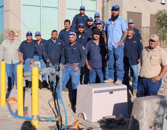 LCU Water Line Maintenance Supervisor, Vince Castillo; Meters, Valves, and Hydrants (tan shirt on the left), LCU Water Line Maintenance Supervisor, Ron Borunda, (tan shirt on the right). The supervisors stand with their crews who spent a straight 48 hours on University Avenue after a water main failure, which began on Sept. 5, 2019.