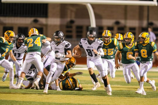 Sophomore quarterback Beto Garcia (81) runs the ball as the Mayfield Trojans face off against the Oñate Knights at the Field of Dreams in Las Cruces on Friday, Sept. 27, 2019.