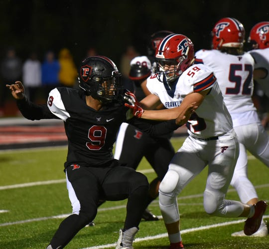 Livonia Churchill Charger Khalil Ford, left, goes up against Franklin offensive lineman Will Linton.