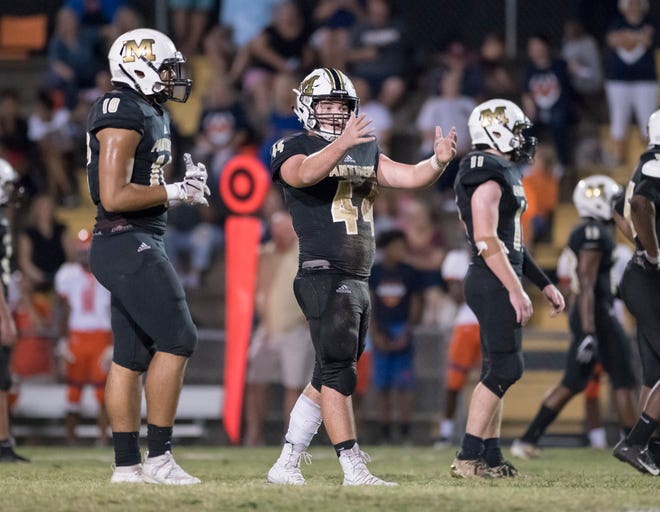 Trevor Lunsford (44) communicates with teammates in between plays during the Escambia vs Milton football game at Milton High School on Friday, September 27, 2019.