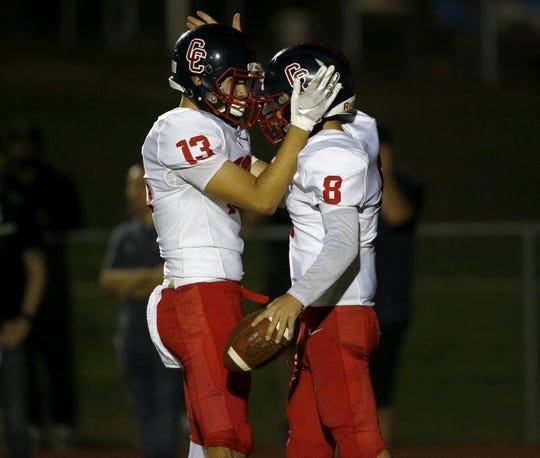 Centennial's Brad Young (13) and Jonathan Morris (8) celebrate a touchdown against Millennium on Sept. 27.