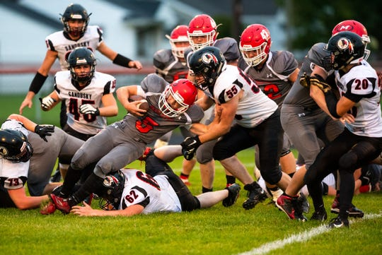 Marlette running back Ian Schetter (5) is tackled by Sandusky's Casey Kirkpatrick (55), with help from Riley Franzel (62) during the first quarter of their game Friday, Sept. 27, 2019, at Marlette High School.