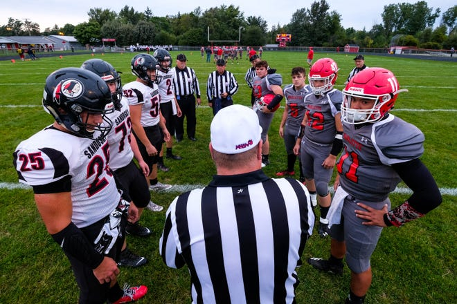 Captains from both Sandusky and Marlette high schools huddle for the coin toss before their Week 5 Greater Thumb Conference East game Friday, Sept. 27, 2019, at Marlette High School.