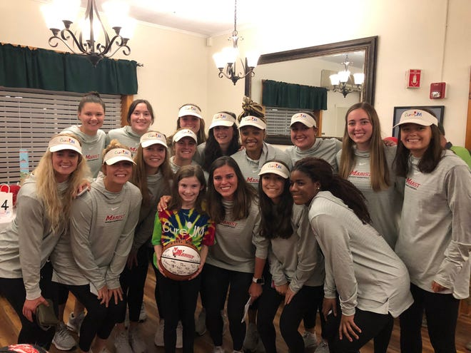 The Marist College women's basketball team poses with Maddie Clements, an 11-year-old Red Hook girl who, like Kendall Krick, is battling a rare disease.