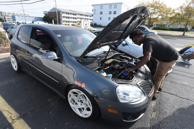 Ishmael Bracy of Philadelphia works on his 2008 VW Golf in the parking lot of the shopping center at 127th St. at the unofficial H2Oi event in Ocean City Saturday, September 28, 2019.
