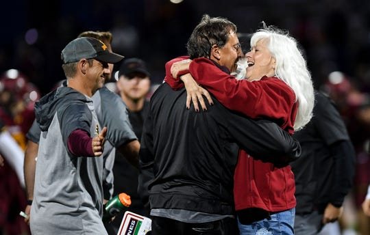 """Sioux Falls Roosevelt football coach Kim Nelson is greeted by his wife, Shelly, as he becomes the """"winningest"""" high school football coach ever in South Dakota after the Rough Riders' win on Friday, September 27, at Howard Wood Field in Sioux Falls."""