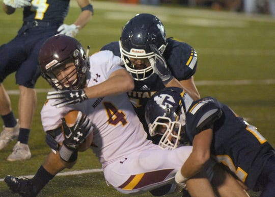 Madison's Jacob Unterbrunner is brought down by two Tea Area players Friday, Sept. 27, in Tea.