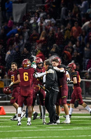 """Sioux Falls Roosevelt football coach Kim Nelson is doused in water by his team after becoming the """"winningest"""" high school football coach ever in South Dakota after the Rough Riders' win on Friday, September 27, at Howard Wood Field in Sioux Falls."""