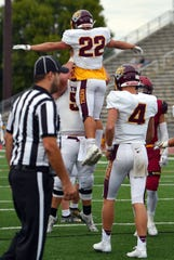 A Harrisburg player lifts Anders Clayton off the ground after Clayton scored a touchdown during a game against Sioux Falls Roosevelt on Friday, September 27, at Howard Wood Field in Sioux Falls.