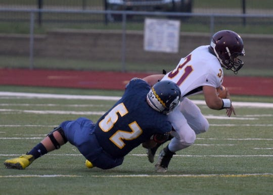 Madison's Chris Reece is brought down for a loss by Tea Area's Luke Rettedal on Friday, Sept. 27, in Tea.