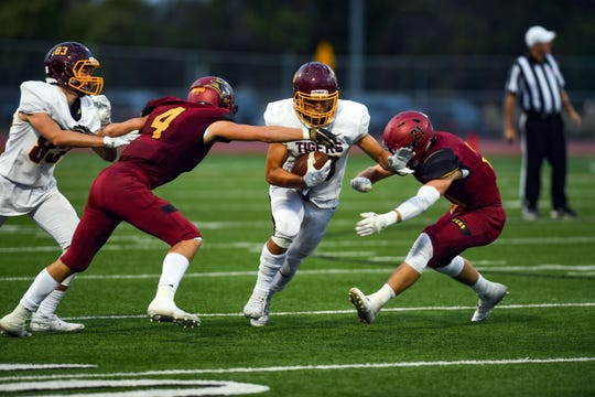 Jhei Roewart of Harrisburg runs the ball between Roosevelt's defense during their game on Friday, September 27, at Howard Wood Field in Sioux Falls.