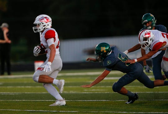 Reeds Spring junior Matt Allison carries the ball as Springfield Catholic's Chase Haynes misses a tackle during a game at Catholic on Friday, Sept. 27, 2019.