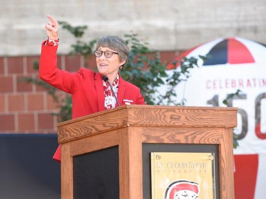 SCSU president Robbyn Wacker points to cheering alumni at the dedication of Husky Plaza Saturday, Sept. 28, 2019.
