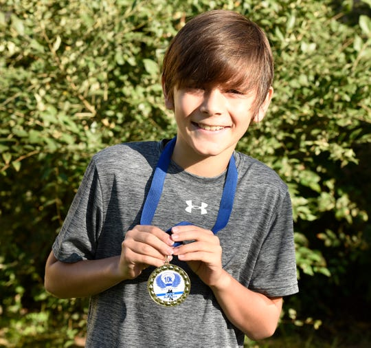 Kade Lovell, 9, smiles with his medal for winning the St. Francis Xavier Franny Flyer 10k on Saturday, Sept. 28, 2019. Lovell accidentally won the 10k last weekend after only planning on completing the 5k.