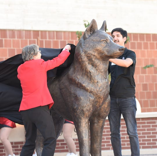 A bronze husky statue is unveiled by Kridish Uprety, student government association president, and SCSU president Robbyn Wacker in newly-built Husky Plaza Saturday, Sept. 28, 2019, at SCSU.