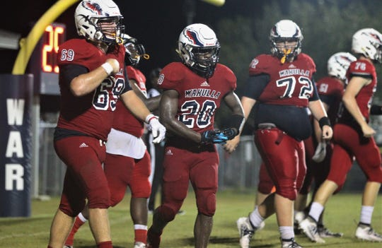Wakulla running back Jordan Bolden (20) rocks a baby to sleep after a touchdown run as the War Eagles beat Godby 35-25 on Friday, Sept. 27, 2019.