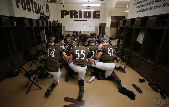 The Austin Panters football team gathers in the center of their locker room to pray before their game Friday against Andress.