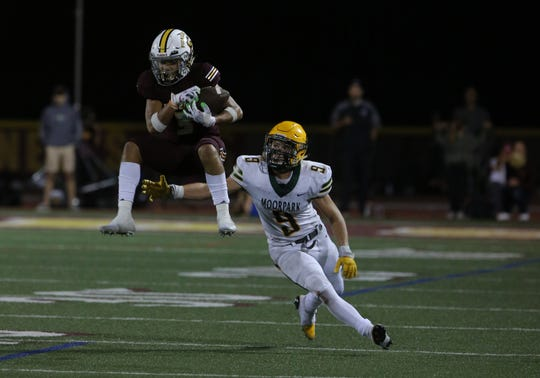 Simi Valley High's Malik Hunt makes a jumping catch in  front of Moorpark's Ashton Benner during Friday night's game. Simi won 37-34.