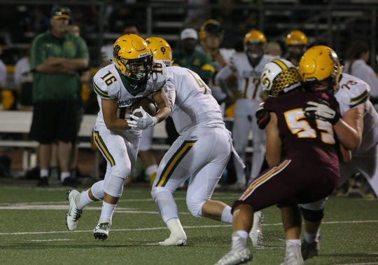 Moorpark High's Tyler Salinas takes the handoff from quarterback Blake Sturgill during the second quarter of Friday night's game against Simi Valley.