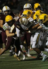 Simi Valley High's Ranell White is sandwiched between a group of Moorpark linemen during Friday night's game. Simi won 37-34.