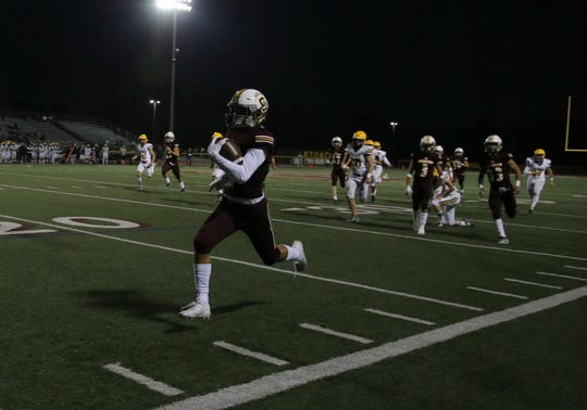 Simi Valley High's Elijah Leiva scores on a kickoff return in the first quarter during Friday night's game against Moorpark. Simi won 37-34.
