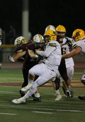 Moorpark High quarterback Blake Sturgill is taken down by Simi Valley High's Fernando Rodriquez during the second quarter of Friday nigh's game.