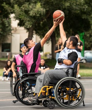 Wheelers's Alex Simonson, right, play against a group of El Diamante High schooll students in basketball during Kaweah Delta Rehabilitation Hospital's first Adaptive Sports and Equipment Expo on Saturday, Sept. 28, in Visalia. The El Diamante students are part of Visalia Unified School DistrictÕs (VUSD) Sports Therapy, Rehabilitation, Orthopedics, and Neuromuscular Gains (STRONG) Academy. The linked learning academy is comprised of high school students who are interested in careers as athletic trainers, physical therapists, orthopedic surgeons, registered nurses, doctors and more. Wheelers are from the Valley ChildrenÕs Adaptive Sports ProgramÕs team.