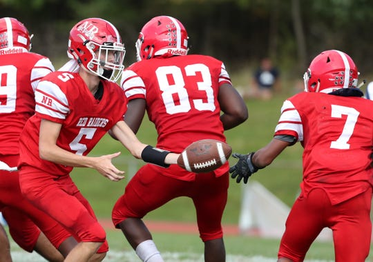 North Rockland quarterback Anthony Morina (5) hands off to AJ Johnson (7)  during their 18-10 win over Suffern at North Rockland High School in Thiells on Saturday, September 28, 2019.
