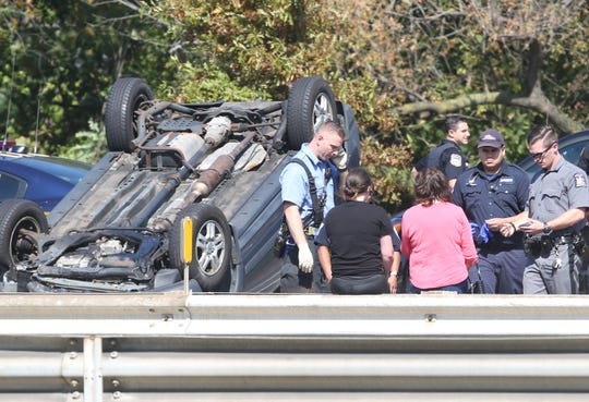 First responders check on the condition of the two people that were in a car that rolled over on westbound Interstate 287 near Exit 7 in White Plains Sept. 28, 2019. The occupants were uninjured. Traffic westbound was backed up for miles.
