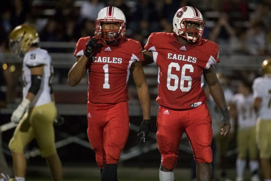 Smyrna's Darryl Williams (1) and Hugo Harp (66) celebrate a sack Friday night against Salesianum. Smyrna defeated Salesianum 18-10.
