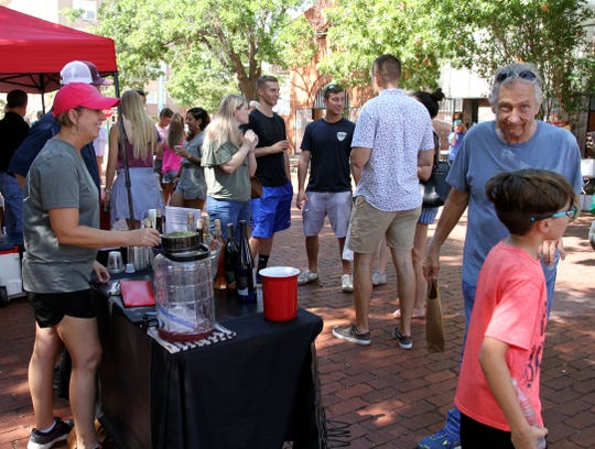 People walk around and taste wines from local wineries Saturday, Sept. 28, 2019, in the Wichita Falls Farmers Market Fall Wine Festival.