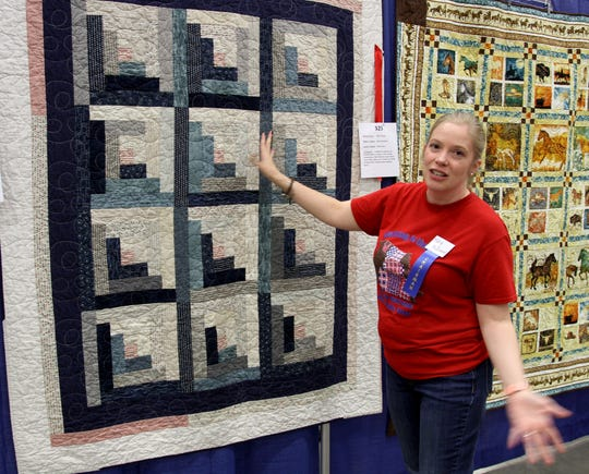 Mary McElvain, quilt show chairman, shows off a traditional quilt she made Saturday, Sept. 28, 2019, at the Red River Quilters' Guild Quilt Show in the Ray Clymer Exhibit Hall.