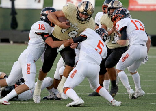 Rider's Jacob Rodriguez is tackled by Dumas' Josh Turner (16) and Javier Martinez (5) Friday, Sept. 27, 2019, at Memorial Stadium.