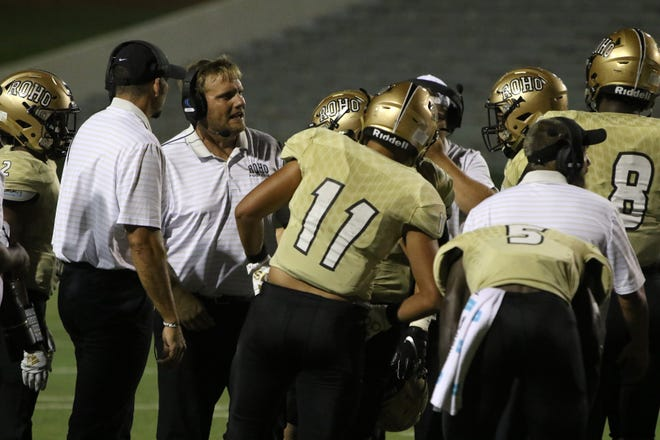 Rider head football coach Marc Bindel talks to his players during a timeout in the game against Dumas Friday, Sept. 27, 2019, at Memorial Stadium.
