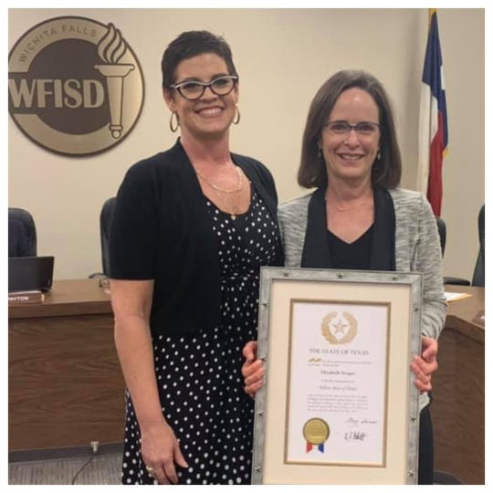 Wichita Falls High School Principal Christy Nash presented WFISD Board President Elizabeth Yeager with a Yellow Rose of Texas Commission at recent school board meeting.