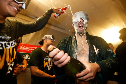 Beginner athletics pitcher Mike Fiers celebrates with teammates.
