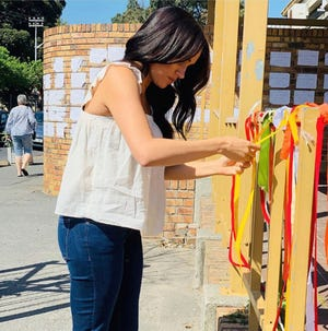 "In this handout photo taken from the Sussex Royal instagram account, Britain's Meghan, the Duchess of Sussex visits the memorial to a murdered South African student as a ""personal gesture"" after ""closely following the tragic story""."