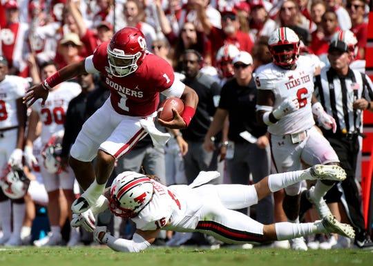 Oklahoma quarterback Jalen Hurts jumps over Texas Tech defensive back Thomas Leggett during the second quarter at Gaylord Family - Oklahoma Memorial Stadium.
