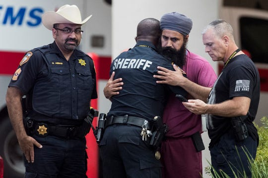 Mourners gather outside Memorial Hermann Hospital in Houston after Harris County Sheriff's Deputy Sandeep Dhaliwal was transported to the medical examiners office after he was shot and killed in the line of duty on Sept. 27, 2019.