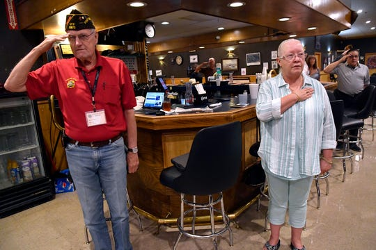Members of VFW Post 6873 salute during the Pledge of Allegiance at the start of Sunday's celebration of the national organization's 120th anniversary.